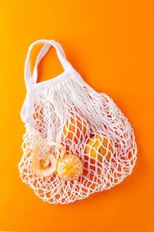 Mandarini piatti in un sacchetto della spesa a rete, concetto zero rifiuti