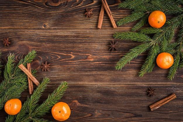Mandarini su legno con rami di abete di natale