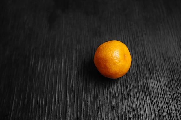 Mandarini su uno sfondo nero. molta frutta fresca - mandarini.