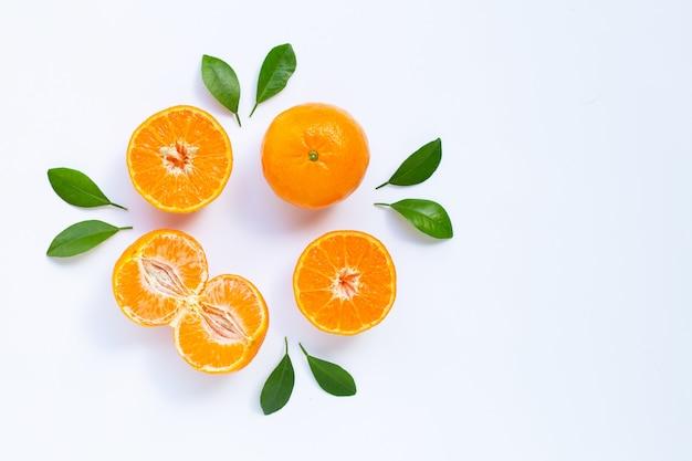 Mandarino fresco con foglie su sfondo bianco.