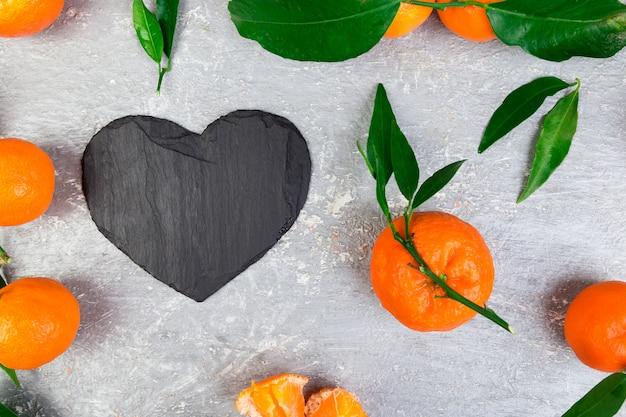 Mandarino intorno con ardesia nera a forma di cuore.