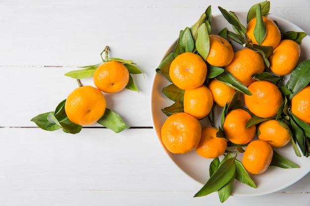 Mandarino mandarini con foglie in un piatto bianco. vista dall'alto,