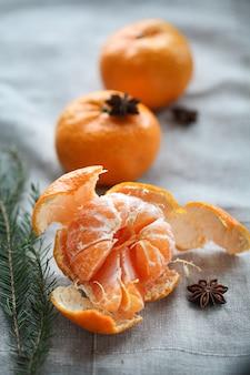 Mandarino maturo sbucciato su superficie grigia, anice stellato.