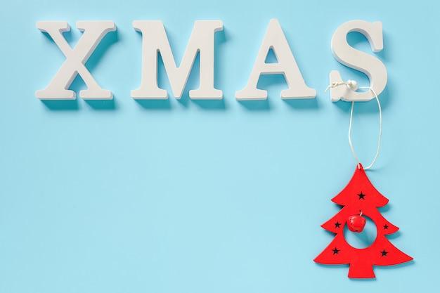 Mandi un sms a natale dalle lettere bianche e dal giocattolo rosso dell'albero della decorazione di natale su fondo blu