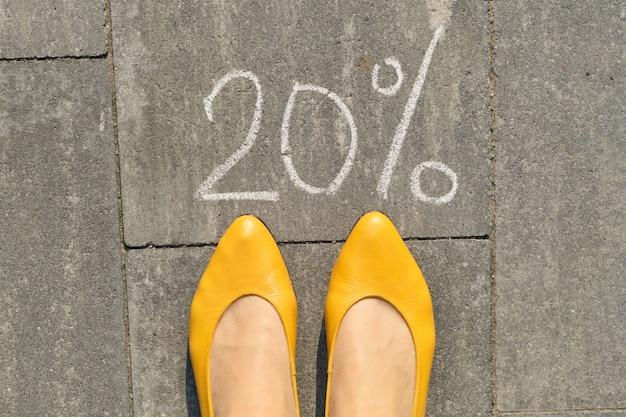 Mandi un sms al 20 per cento scritto su pavimentazione grigia con le gambe della donna
