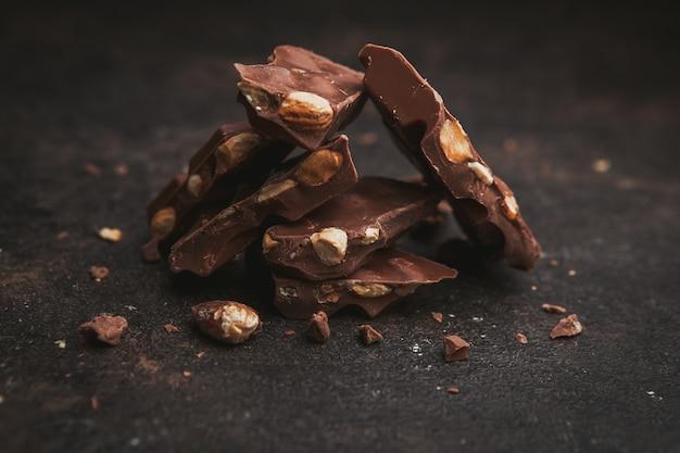 Mandorla alta vista con cioccolato su marrone scuro.