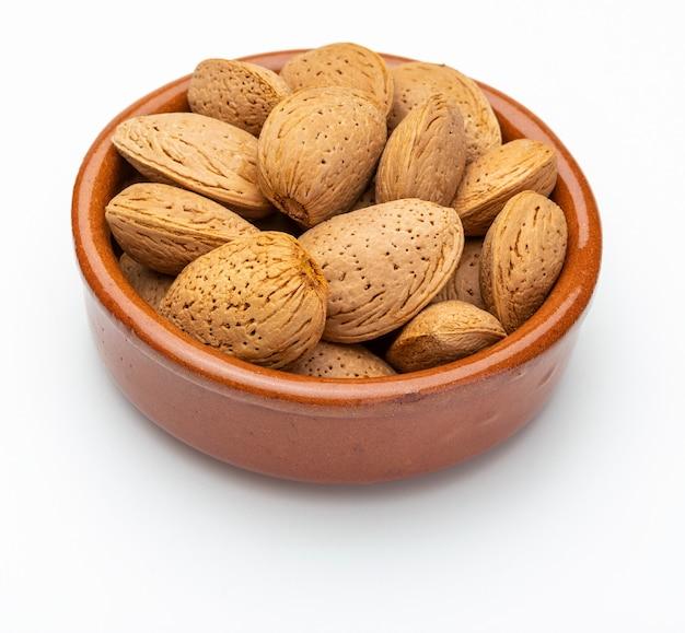 Mandorle con guscio in ciotola di argilla (raccolta di vari tipi di noci). isolato