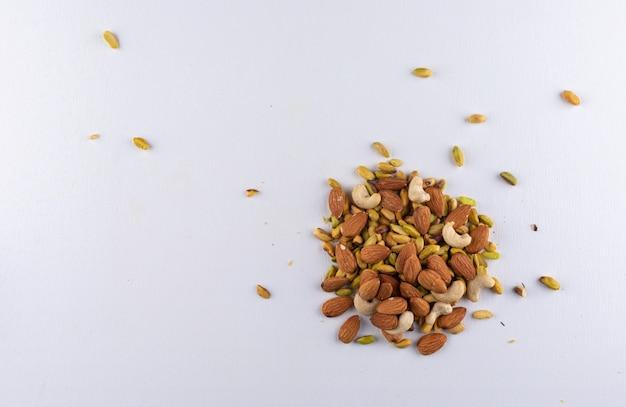 Mandorle ed anacardi dei pistacchi di vista superiore sull'orizzontale bianco