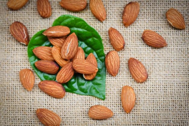 Mandorle sul fondo del sacco con la foglia verde - alto vicino dell'alimento della proteina naturale delle noci della mandorla e per lo spuntino