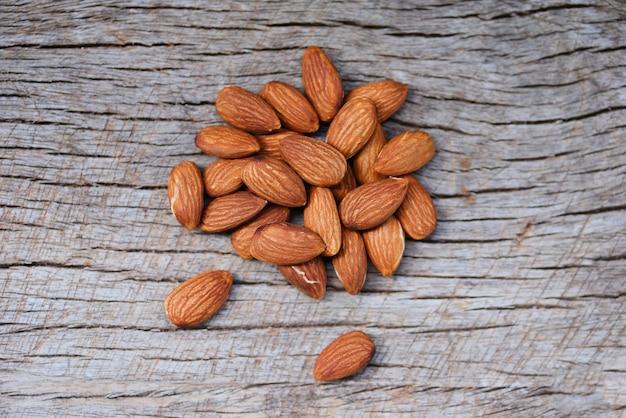 Mandorle sulla vista superiore del fondo di legno rustico - alto vicino dell'alimento della proteina naturale delle noci della mandorla e per lo spuntino