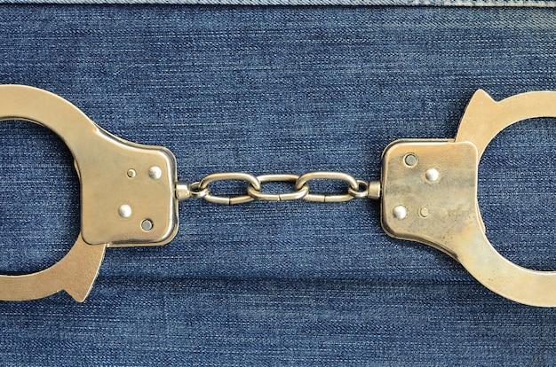 Manette d'acciaio della polizia che si trovano sul fondo blu scuro delle jeans