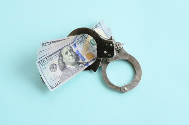 Manette d'argento della polizia e cento fatture del dollaro si trova su blu-chiaro