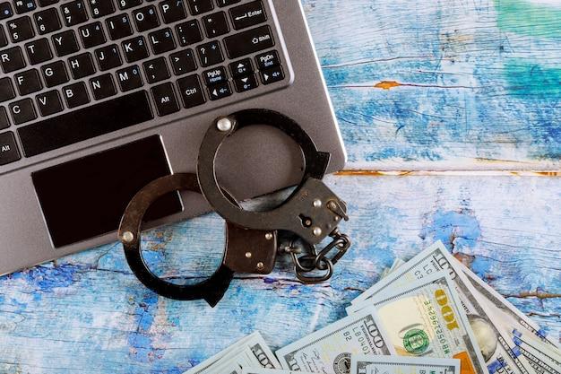 Manette della polizia d'acciaio su un mucchio di banconote da cento dollari con la tastiera del computer, internet cyber crime tecnologia