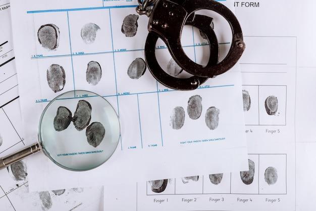 Manette della polizia e carta di impronte digitali criminali, con lente d'ingrandimento, vista dall'alto