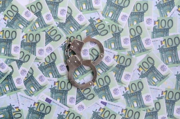 Manette della polizia si trova su un insieme di denominazioni monetarie verdi di 100 euro. un sacco di soldi formano un mucchio infinito