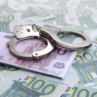 Manette della polizia si trova su un insieme di denominazioni monetarie verdi di 100 euro