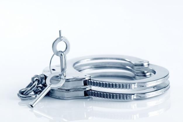 Manette in metallo e chiave nel buco della serratura