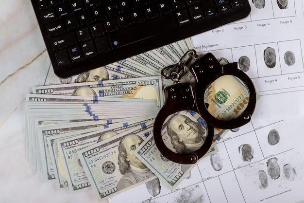 Manette su banconote da cento dollari con la tecnologia della tastiera del computer dell'impronta digitale