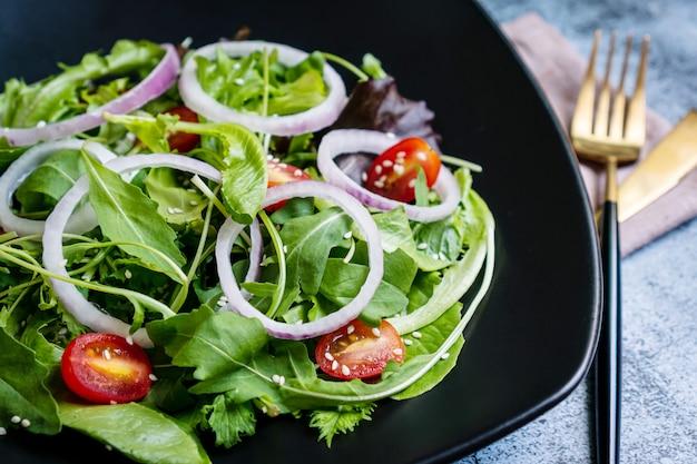 Mangi il concetto verde con l'insalata organica della verdura fresca in piatto ceramico su fondo nero.