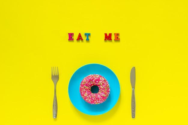 Mangiami ciambella rosa sul piatto blu e forchetta coltello posate su sfondo giallo.