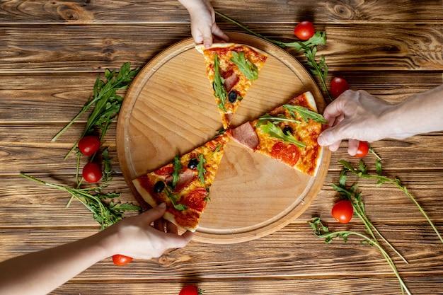 Mangiare cibo. primo piano delle mani della gente che prendono le fette di pizza di peperoni. gruppo di amici che dividono insieme pizza.