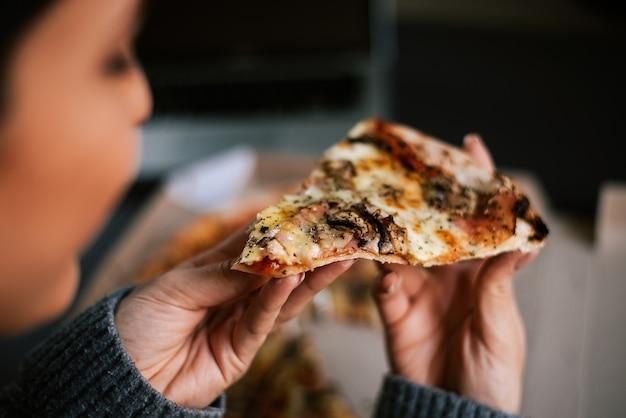Mangiare la pizza di notte. avvicinamento