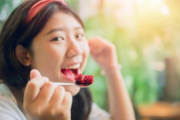 Mangiare la torta. le donne tozze giovani pritty asiatiche sveglie mangiano il dessert in caffè.