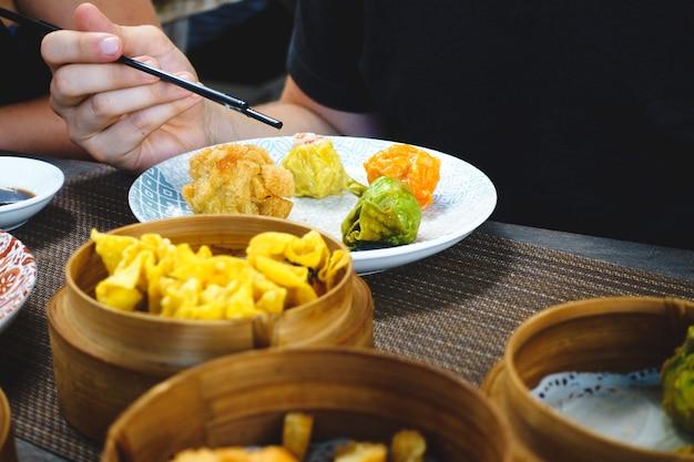 Mangiare panini al vapore e fritti cinesi con bastoncini di chop