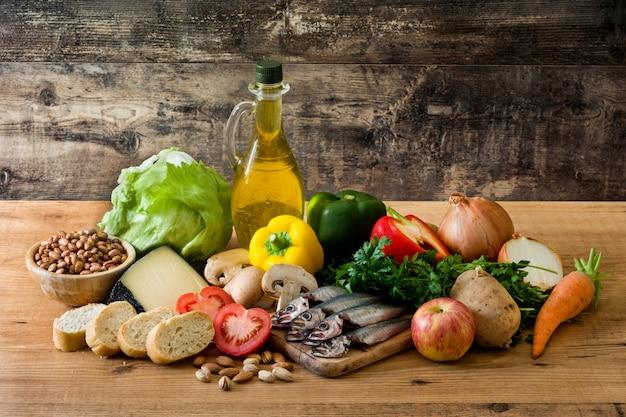Mangiare sano. dieta mediterranea frutta, verdura, grano, olio di oliva matto e pesce sul tavolo di legno