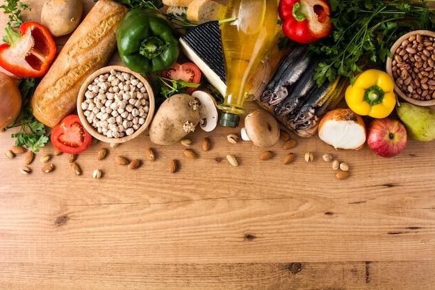Mangiare sano. dieta mediterranea. frutta, verdure, grano, olio d'oliva matto e pesce sulla vista di legno copyspace della cima di tavola