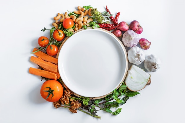 Mangiare sano. piatto ceramico bianco che circonda con l'ingrediente di alimento biologico fresco, le verdure, l'erba e le spezie, su fondo bianco