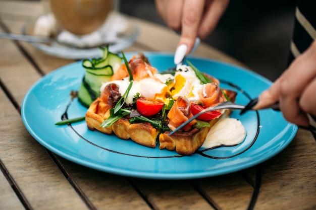 Mangiare waffle toast con uovo in camicia e salmone sul tavolo di legno