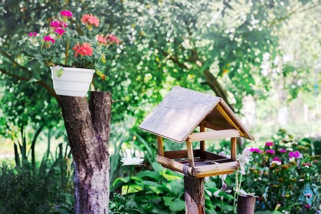 Mangiatoia per uccelli nel giardino vicino a un vaso di fiori. giornata di sole estivo nel parco