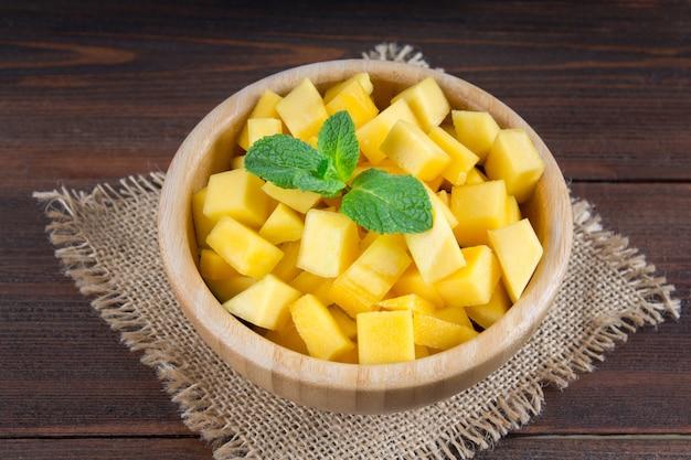Mango della frutta tropicale in un piatto su un fondo di legno, intero o affettato.