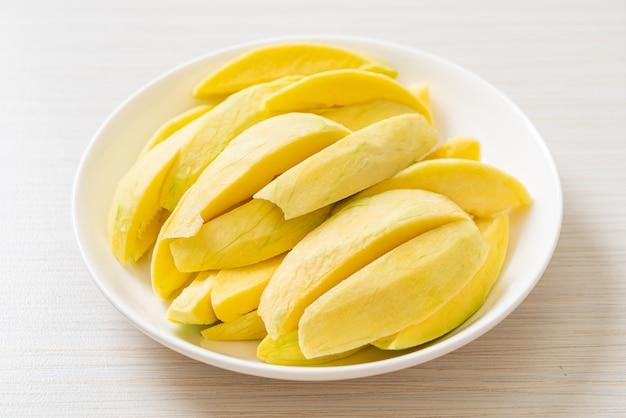Mango verde e dorato fresco affettato sul piatto