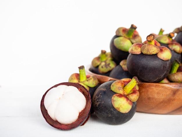 Mangostani (garcinia mangostana) nel piatto di legno e buccia a metà su fondo bianco.