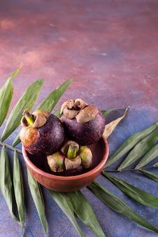 Mangostano della regina dei friuts su una ciotola con foglia di palma su fondo di pietra con lo spazio della copia
