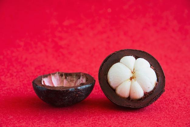 Mangosteen frutti popolari tailandesi - un frutto tropicale con segmenti bianchi succosi e succosi di carne all'interno di una spessa crosta rossiccia-marrone.