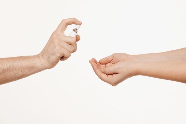 Mani a due paia con spray disinfettante e utilizzo. concetto di igiene e protezione antibatterica. covid-19, concetto di coronavirus. concetto di assistenza sanitaria.
