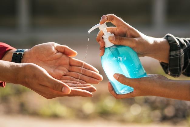 Mani al flacone di gel per lavarsi le mani e spremere gli altri per lavarsi le mani.