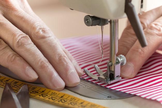 Mani alla macchina per cucire che tiene un certo tessuto