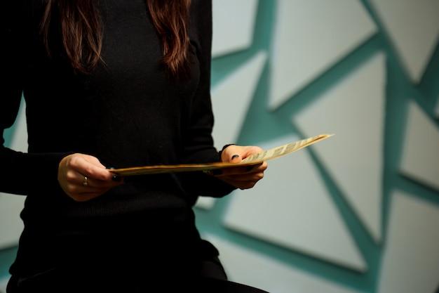 Mani alte e selettive del fuoco della tenuta della ragazza e leggere il giornale