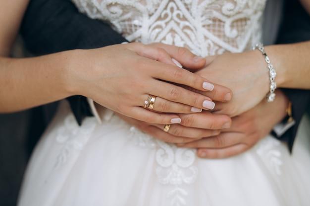 Mani appena della coppia sposata con le fedi nuziali, vista frontale, concetto di matrimonio
