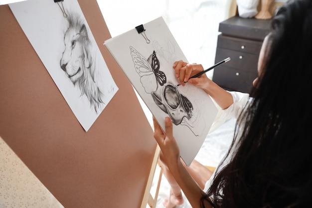 Mani asiatiche dell'artista che disegnano immagine con la matita