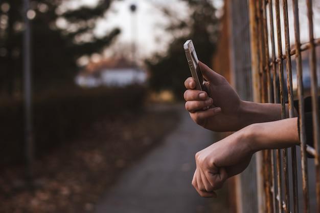 Mani attraverso le barre con il cellulare