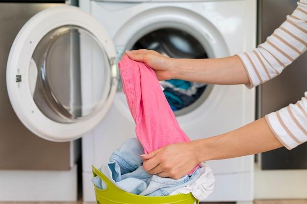 Mani che allungano i vestiti in lavanderia