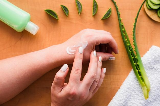 Mani che applicano la crema di aloe vera