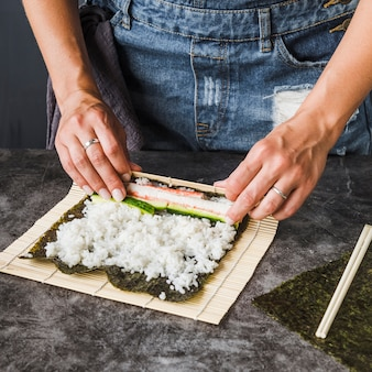 Mani che avvolgono gli ingredienti sulla stuoia di sushi