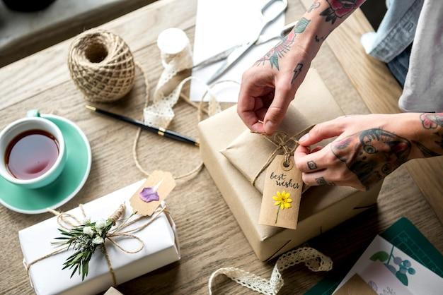Mani che avvolgono scatola regalo con decorazione floreale