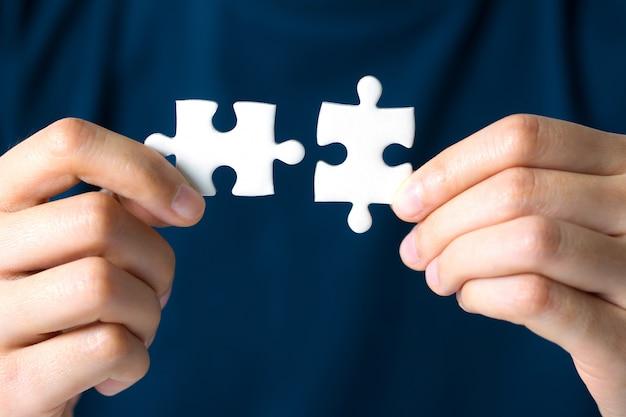 Mani che collegano jigsaw puzzle. soluzioni aziendali, successo e concetto di strategia.